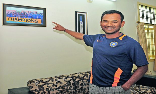 R. Sridhar, newly appointed fielding coach of the Indian cricket team, points to a frame of the Indian U-19 side he had coached to the U-19 World Cup win in 2012 in Australia that hangs on the wall of his house in Hyderabad in this file photo. (Photo: Deccan Chronicle)