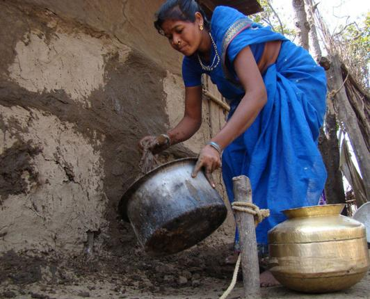 A Gond adivasi woman washes the mud walls of her home with liquid cowdung at Keslapur in Adilabad. Photo: S. Harpal Singh / The Hindu